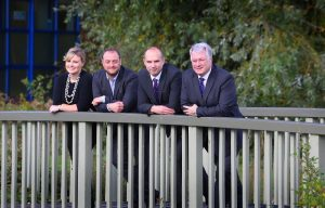 3 men and a woman stood on a bridge outside of an office