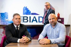 2 men sat at a table with another man and BIAD logo in the background