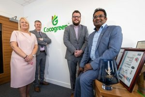 3 men and a woman in a Cocogreen office gathered around an some awards on a table