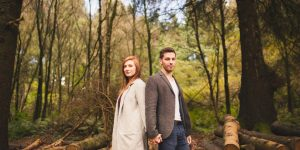 A man and a woman holding hands and posing in a forest