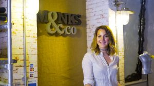 A woman stood in front of a Monks & Co sign with brick walls and a mannequin in the background