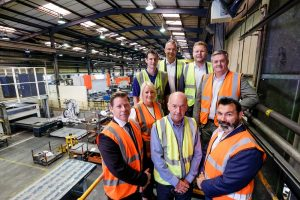A group of employees from Newfield Fabrications Limited stood in Hi Vis jackets in a warehouse