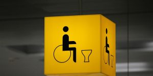 A yellow cube sign, lit up with an icon of a person in a wheel chair and a toilet silhouette