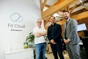 3 men standing in the Fit Cloud office with desks in the background