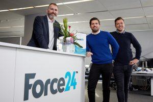 3 men stood near a Force 24 branded reception desk in an office