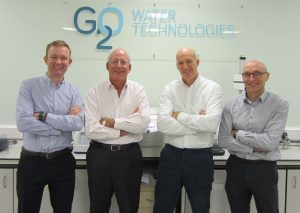 4 men stood with their arms crossed in an office with G20 Water Technologies logo on the wall behind them