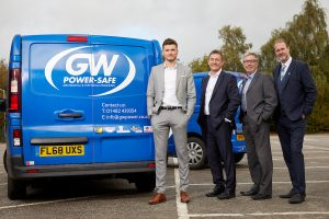 4 men in suits stood in a car park next to GW Power Safe vans