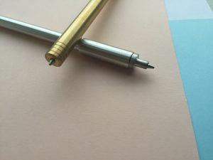 A gold and silver pen resting on top of a notebook