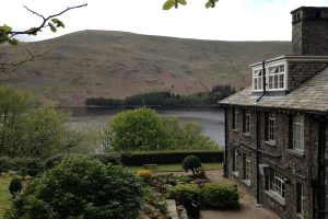 Exterior of Haweswater Hotel surrounded by trees, a lake and hill