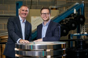 2 men in suits stood in a metal supplier factory