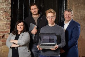3 men and a woman from Horizon guides smiling with one man holding an open laptop and one man holding a closed laptop