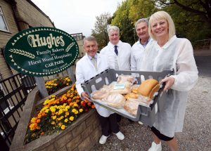 3 men and a woman stood outside of Hughes Bakers holding a basket of fresh bread