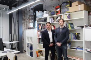 2 men from Simul Software stood in an office with a shelves of books and boxes in the background