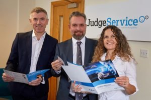 2 men and a woman stood in an office holding some brochures with a Judge Service Research logo on the wall behind them