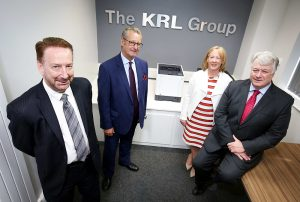 3 men and a woman stood in a meeting room with The KRL Group name on the wall and a printer in between them