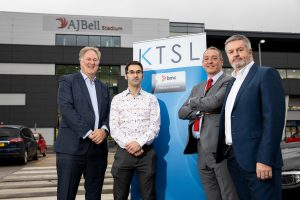 4 men in suits stood in a car park outside of the AJ Bell Stadium with a KTSL pop up banner between them