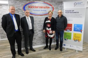 3 men and a woman stood in an office with Kidderminster logo on a brick wall and a MEIF pop in banner next to them