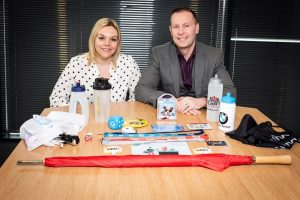A man and a women sat at a table showing their Branded Items Group products
