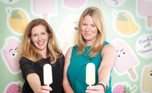 2 women from Claudi and Fin holding an ice cream stood in front of a ice cream design wallpaper