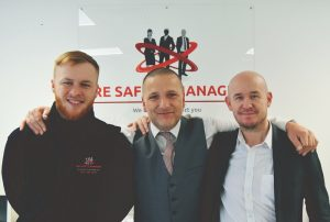 3 men smiling with their arms around each other with the Fire Safety Managers logo in the background