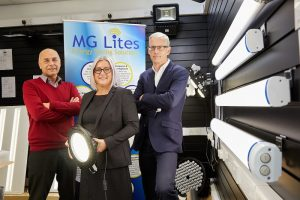 2 men and a woman stood around energy saving equipment with an MG Lites Energy Saving Solution pop up banner in the background