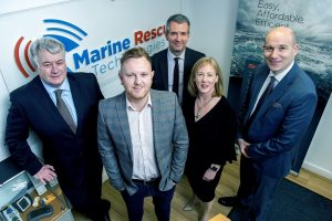 4 men and a woman stood in an office with Marine Rescue Technologies sign in the background