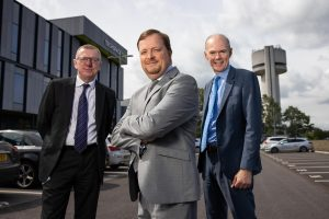 3 men in suits smiling and stood in a car park outside an office building