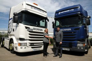 A man and a women shaking hands in front of 2 Motrans lorries