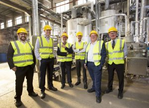 6 men in Hi Vis jackets and hard hats stood in a waste biomass factory