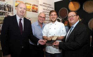 4 men smiling holding a plate of pates and terrines
