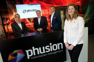 3 men and a woman stood near a Phusion branded counter and TV screen