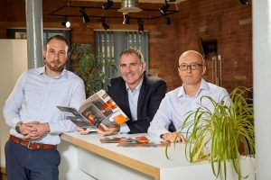 3 men stood around a reception deck with one man holding a Project:ffe brochure