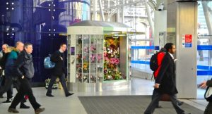 Commuters walking past a Rockflower kiosk at the exit of a London Underground station