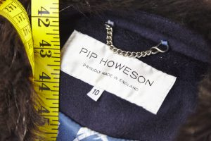 A close up of a Pip Howeson clothes label with a tape measure on top