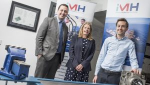 2 men and a woman stood in an office behind some hydraulics equipment with iMH pop up banners in the background