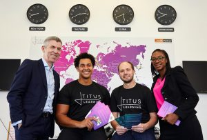 Four employees from Titus Learning standing in front of a world map and clocks