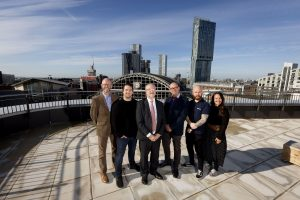 A group of employees from Node Technologies stood outdoors with the city of Manchester in the background