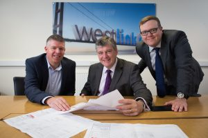 Three men from Westlink Joiners and Locksmiths sat around table holding papers