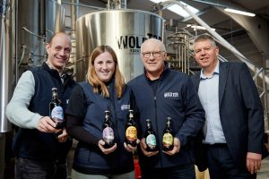 A group of Wold Top Brewery Colleagues holding beer bottles in their Brewery