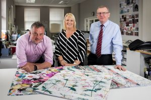 Colleagues from Yellow Label Designs standing in their office and presenting their printed fabrics