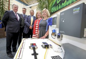 Two women and three men stood next to electrical equipment