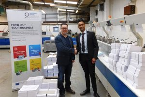 2 men shaking hands in a print lamination warehouse with stacks of paper besides them