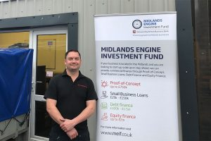 A man from GHO Pressings stood outside of an office building with a Midlands Engine Investment fund pop up banner next to him