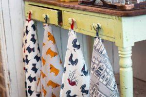 Printed tea towels hanging on rustic drawer knobs