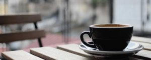 A cup of coffee resting on a wooden table