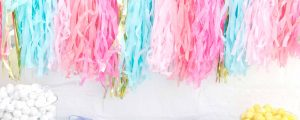 Decorative shredded tissue paper in a variety of colours hanging from the wall