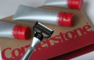 A close up of a razor with a Cornerstone box and lotions in the background