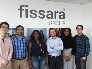A group of employees smiling and stood in front of a Fissara Group branded wall