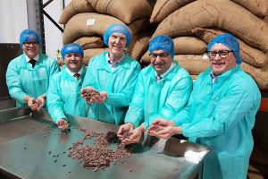 5 men wearing hair nets and overalls while holding cocoa beans