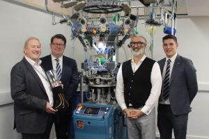 4 men stood next to a textile manufacturing machine